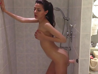 Hot brunette fucks herself with a dildo in the shower