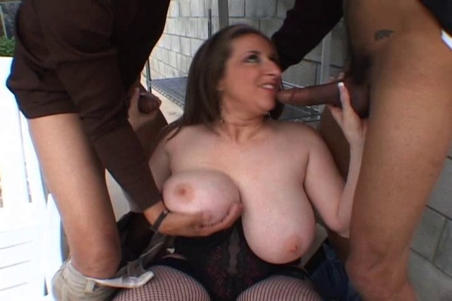 White-girl-is-on-the-ground-showing-her-tits-and-sucking-two-coc