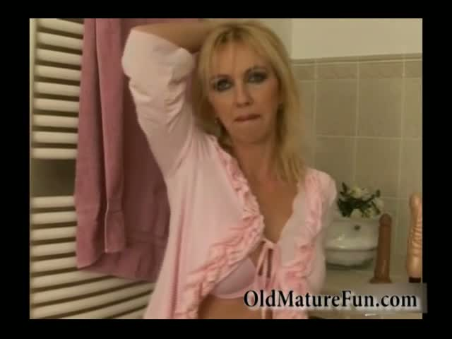 Sexy-friends-mom-in-pink-negligee-does-striptease-in-bathroom