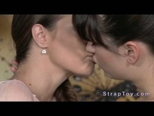 Huge strap on pleasing lesbians in bed